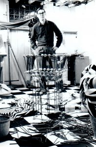 Black and white photograph of the artist Alan Larkin with a tinkertoy tower.